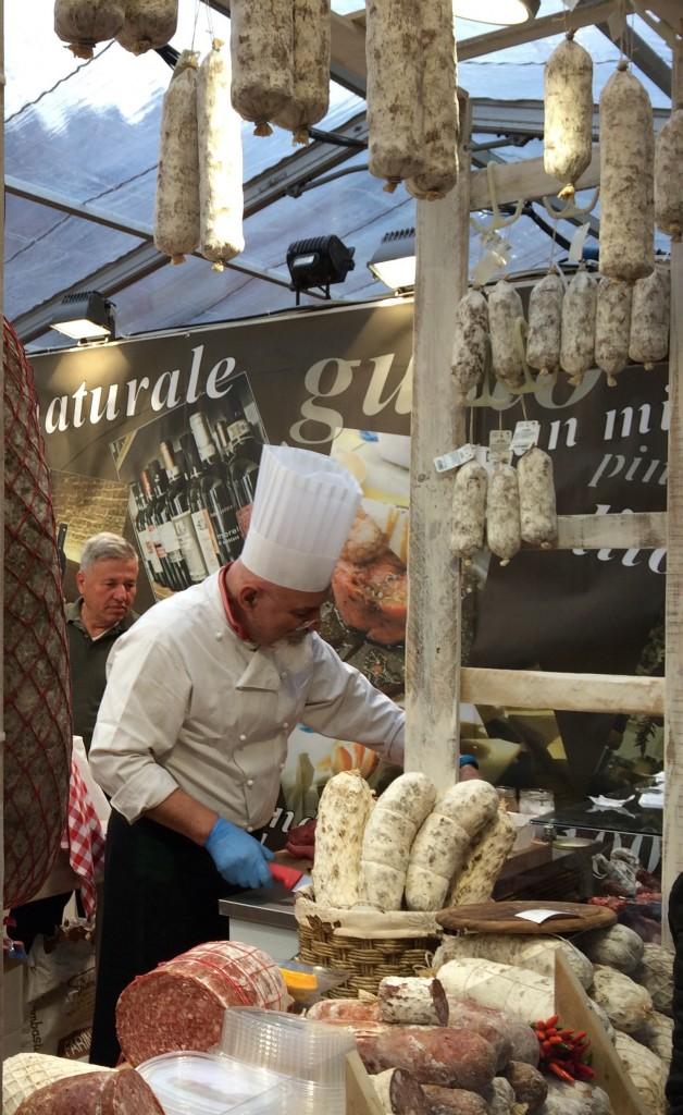 Cook cutting salame in San Miniato